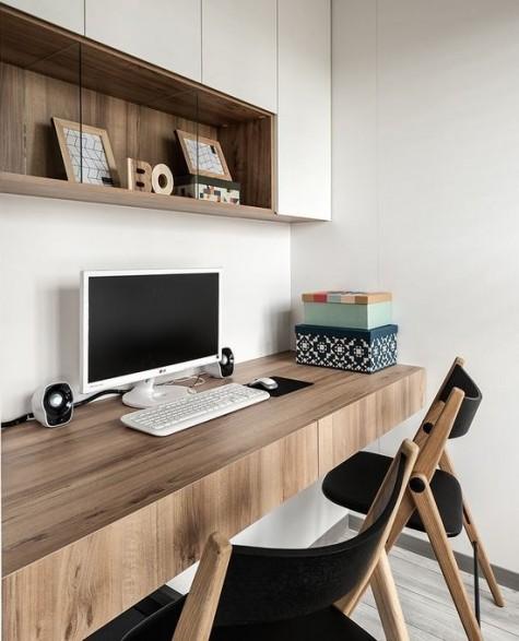 Ein zeitgemäßes Home Office mit einer geschlossenen Aufbewahrungseinheit, einem schwimmenden Schreibtisch mit Schubladen und ein paar Stühlen