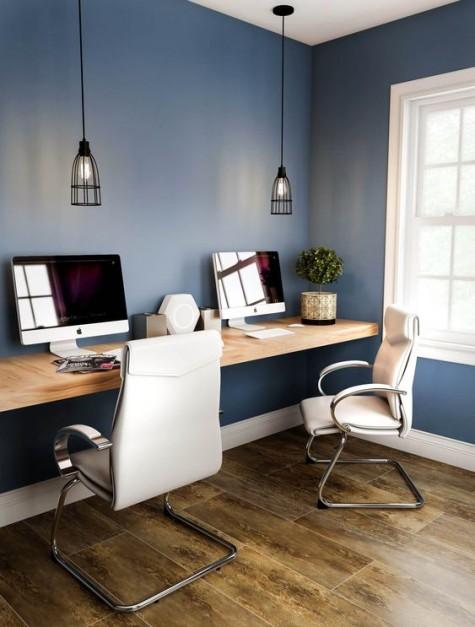 Ein zeitgemäßes Home Office mit schwimmendem Schreibtisch, Ledersesseln und coolen Pendelleuchten
