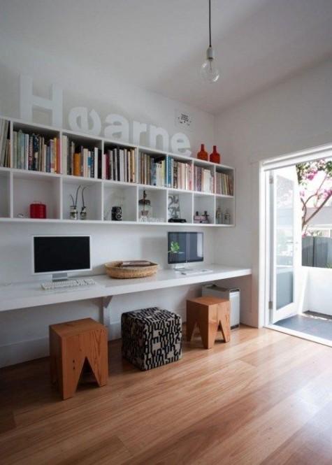 Ein zeitgemäßes Home Office mit großem Regal, schwimmendem Schreibtisch und lichtdurchfluteten Hockern