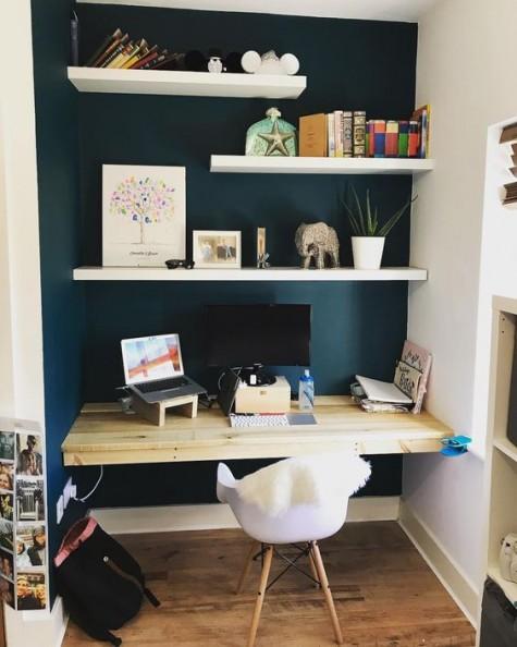 eine marinebemalte Nische, schwimmende Regale, ein schwimmender Schreibtisch und ein weißer Stuhl