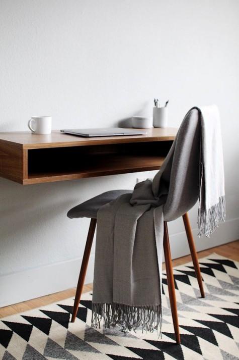 Ein stilvoller, schwimmender Mini-Schreibtisch mit Stauraum und einem Stuhl auf hohen Holzbeinen ist ideal für kleine Räume