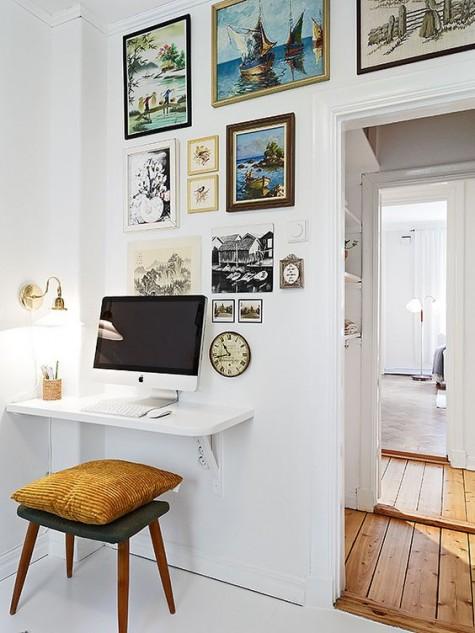 Ein weißer, schwebender Minischreibtisch und ein Hocker mit Kissen, eine Galerie mit Kunstwerken und eine Wandlampe zum Arbeiten