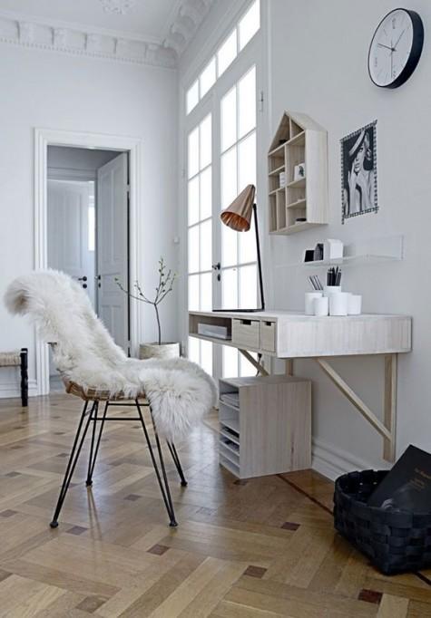 Ein weiß getünchter, schwimmender Schreibtisch mit einigen Schubladen und einem passenden, hausförmigen Regal für einen skandinavischen Arbeitsbereich