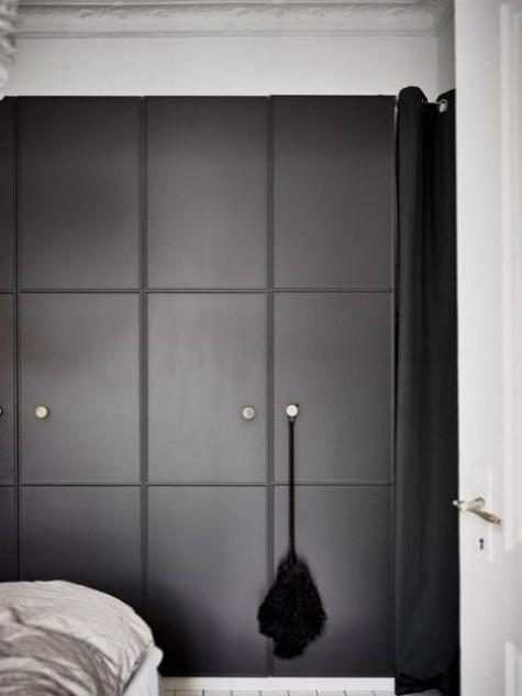 Ein IKEA Pax Kleiderschrank mit schwarz geformten Türen und Metallknöpfen für einen minimalistischen Raum