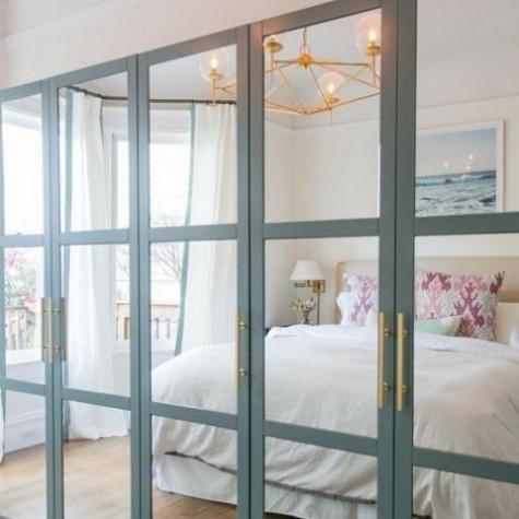 Ein IKEA Pax Kleiderschrank mit voll verspiegelten Fronten mit Aqua-Gestellen und Messinggriffen