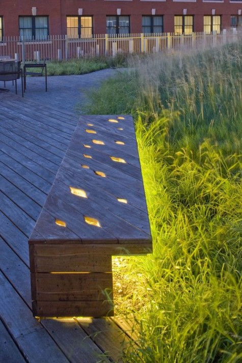 eine Holzbank mit Ausschnitten und Lichtern im Inneren