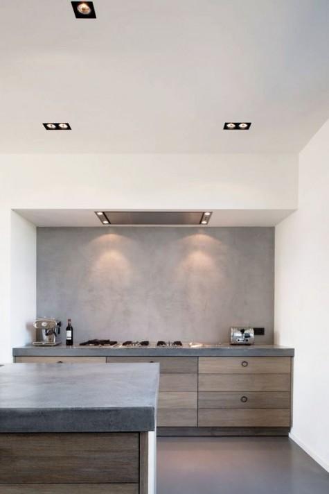 Eine minimalistische und industrielle Küche mit Betonrückwand und Arbeitsplatten sowie Holz als Textur