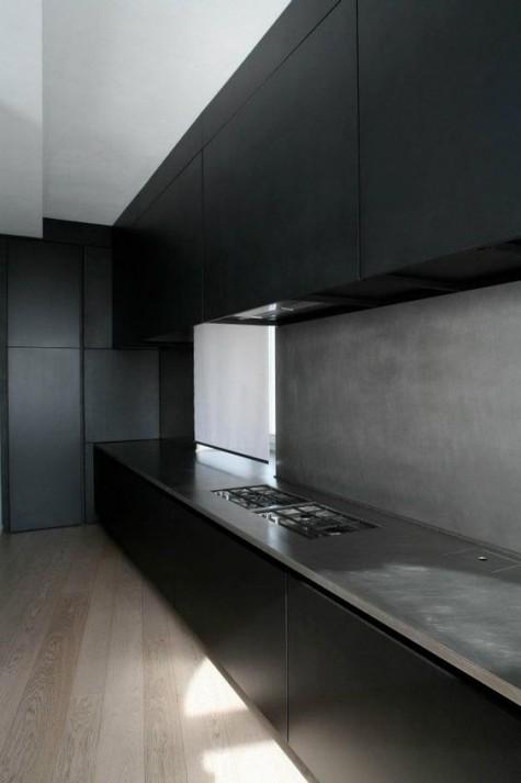 Eine minimalistische schwarze Küche mit Betonboden und Arbeitsplatten für mehr Interesse