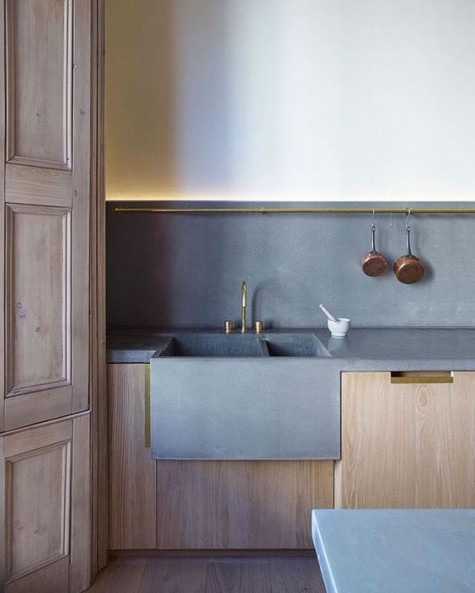 Eine minimalistische Küche mit hellen Holzschränken ist mit Betonelementen kühner gestaltet