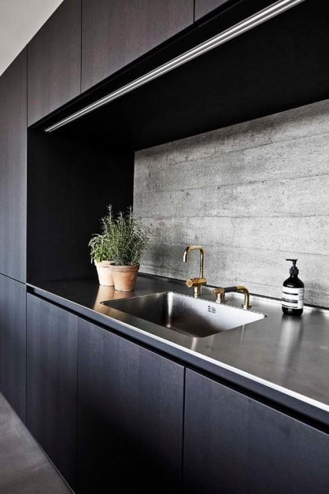 Eine minimalistische dunkle Küche mit einer Betonkante, die Textur verleiht