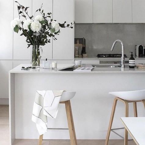 Eine minimalistische, weiße Küche mit einer Betonkante, die dem Raum Textur verleiht