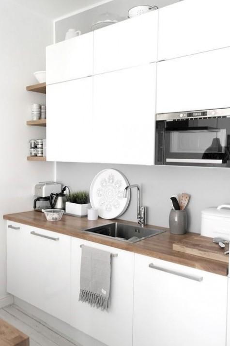 Eine minimalistische weiße Küche mit einer hölzernen Arbeitsplatte und einer glatten Betonrückwand