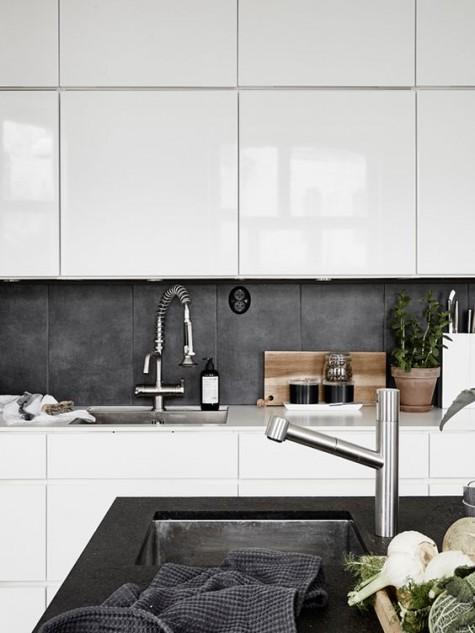Eine weiße, moderne Küche mit Betonfliesen-Aufkantung