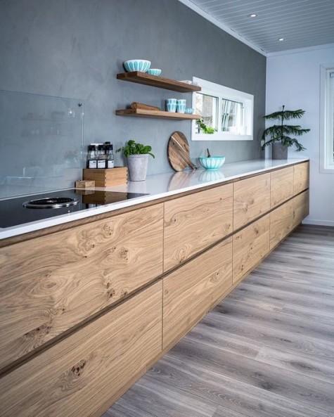 Eine moderne Küche mit Holzkabinen und Betonrückwand sowie einer Glasabdeckung darüber