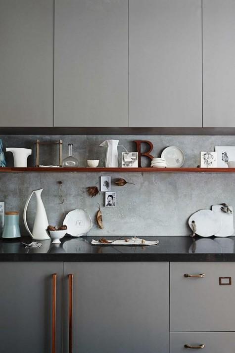 Eine graue Küche mit einer schwarzen Arbeitsplatte und einer Betonkante für einen strukturellen Look