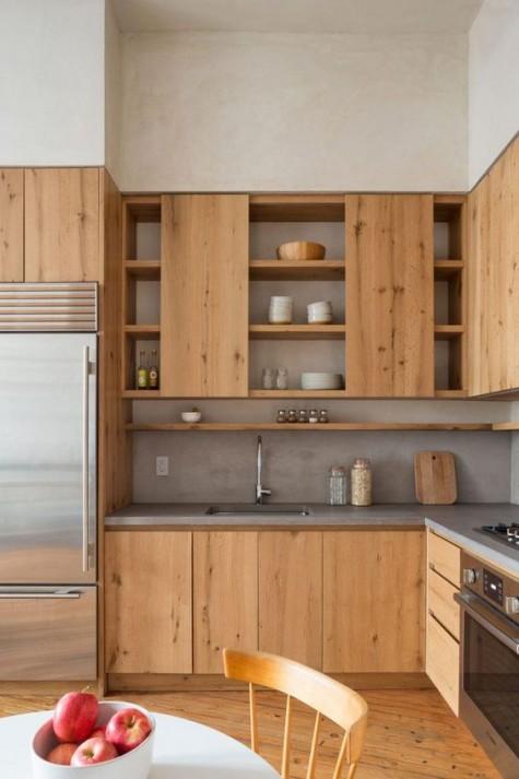 Eine helle Küche aus Holz ist mit Betonplatten und einer Küchenrückwand moderner gestaltet