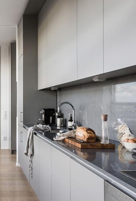 Eine minimalistische hellgraue Küche mit einer Betonrückwand und einer Glasabdeckung, um Spritzer zu vermeiden