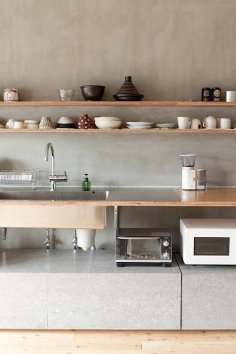 Eine luftige, moderne Küche mit Sperrholzregalen, einer Arbeitsplatte und einer Betonrückwand
