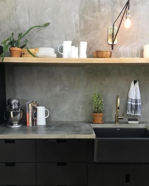 schwarze Industrieschränke, Holzregale und eine Betonrückwand und Arbeitsplatten