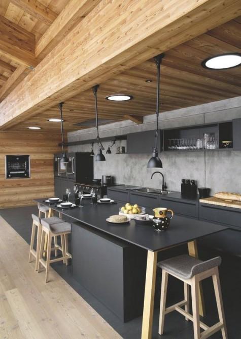Eine ultramoderne Küche mit mattschwarzen Schränken und einer Kücheninsel sowie einer Betonrückwand